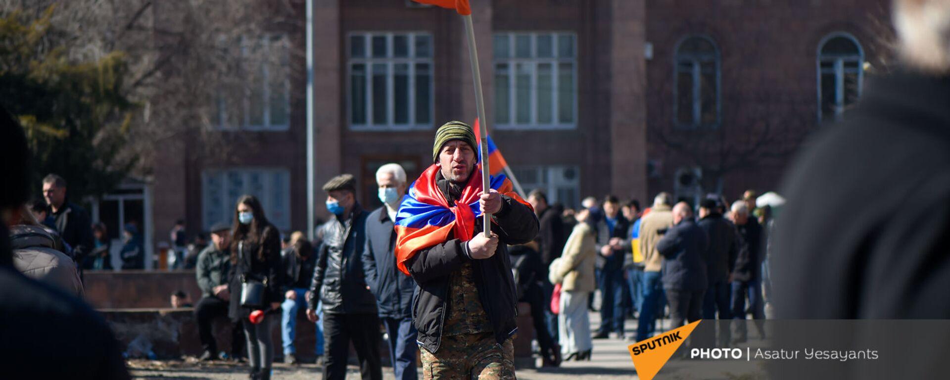 Оппозиционер с флагами на плечах и в руках перед началом акции оппозиции на перекрытом проспекте Баграмяна (26 февраля 2021). Еревaн - Sputnik Արմենիա, 1920, 27.02.2021