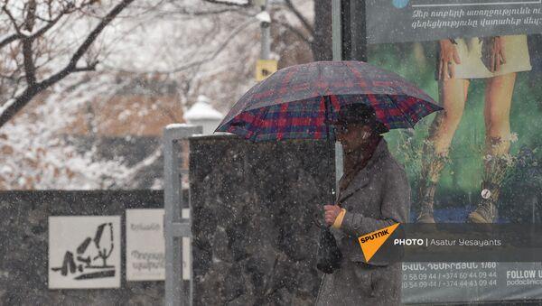 Прохожий с клетчатым зонтом под снегопадом на проспекте Баграмяна (1 марта 2021). Еревaн - Sputnik Армения