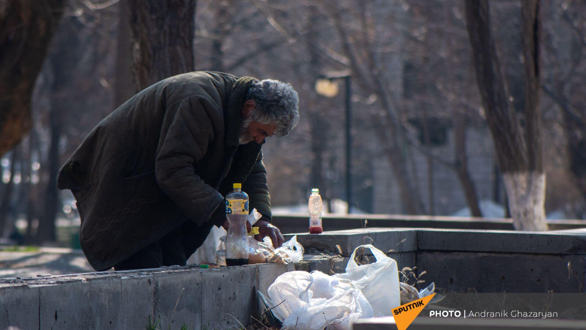 Бездомный мужчина обедает в городском парке - Sputnik Армения, 1920, 14.10.2021