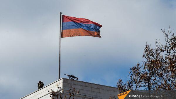 Сотрудник правоохранительных органов рядом с винтовкой на крыше здания МИД Армении (13 марта 2021). Еревaн - Sputnik Армения