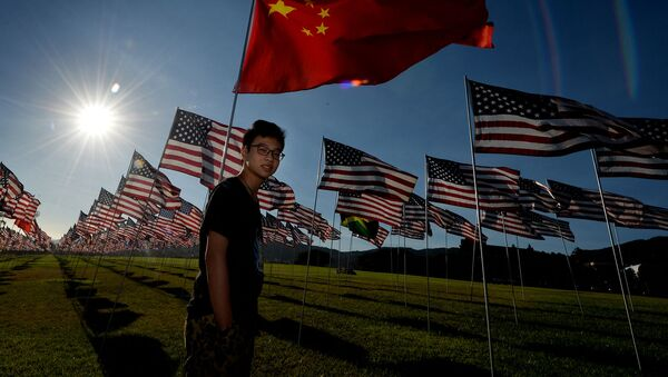 Китайский студент по обмену Джейсон Чай рядом с китайским флагом, находящийся среди флагов США, установленных в память жертвам терактов 11 сентября 2001 (9 сентября 2014). Малибу - Sputnik Արմենիա