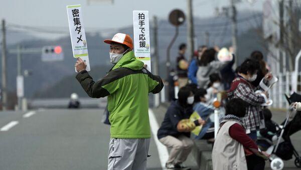Мужчина с табличками во время эстафеты Олимпийского огня в Токио-2020 в префектуре Фукусима, Япония - Sputnik Армения