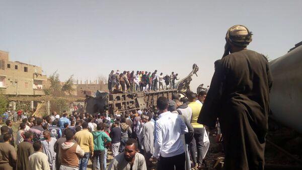 Люди осматривают повреждения после столкновения двух поездов недалеко от города Сохаг (26 марта 2021). Египет - Sputnik Армения