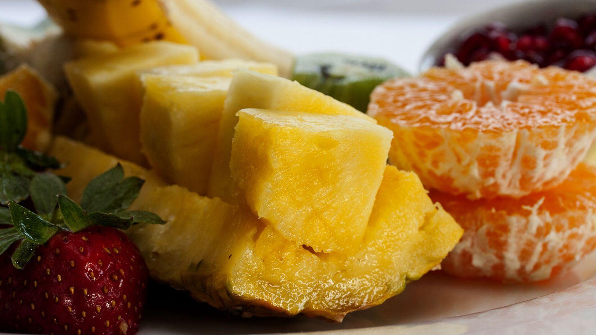 Нарезанный ломтиками свежий ананас с мандаринами и клубникой - Sputnik Армения, 1920, 12.04.2021