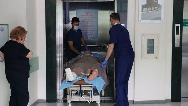 Медики транспортируют получившего ранение спасателя ГСЧС МВД Карабаха в республиканской больнице  - Sputnik Армения