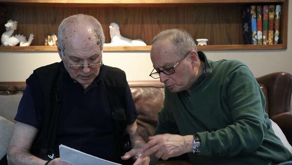 Российский фотограф Валерий Плотников (слева) показывает Сергею Баблумяну альбом со своими фотографиями - Sputnik Армения