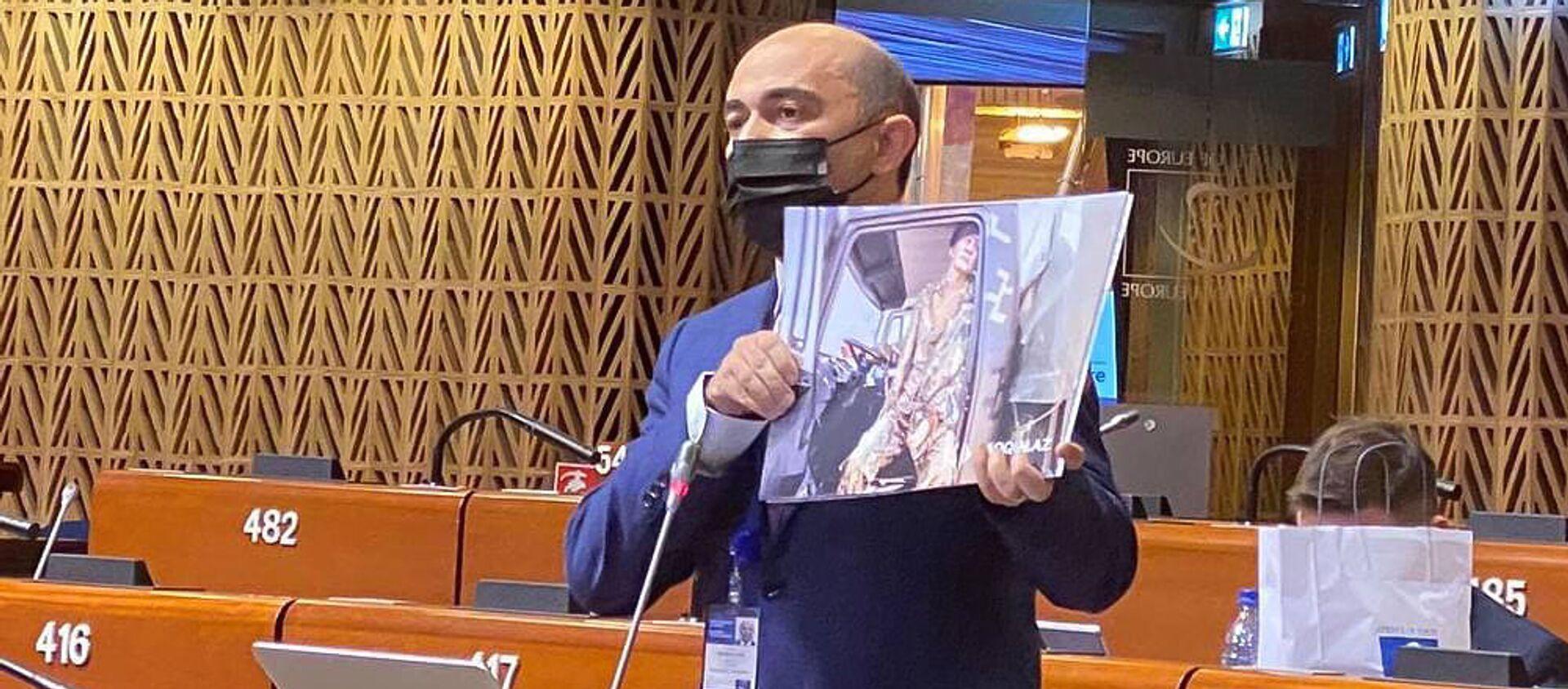 Депутат Эдмон Марукян демонстрирует кадры с Парка военных трофеев в Баку во время Заседания ПАСЕ (19 апреля 2021). Страсбург - Sputnik Արմենիա, 1920, 19.04.2021