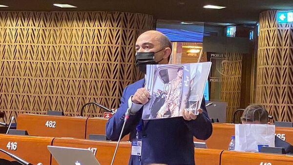 Депутат Эдмон Марукян демонстрирует кадры с Парка военных трофеев в Баку во время Заседания ПАСЕ (19 апреля 2021). Страсбург - Sputnik Армения