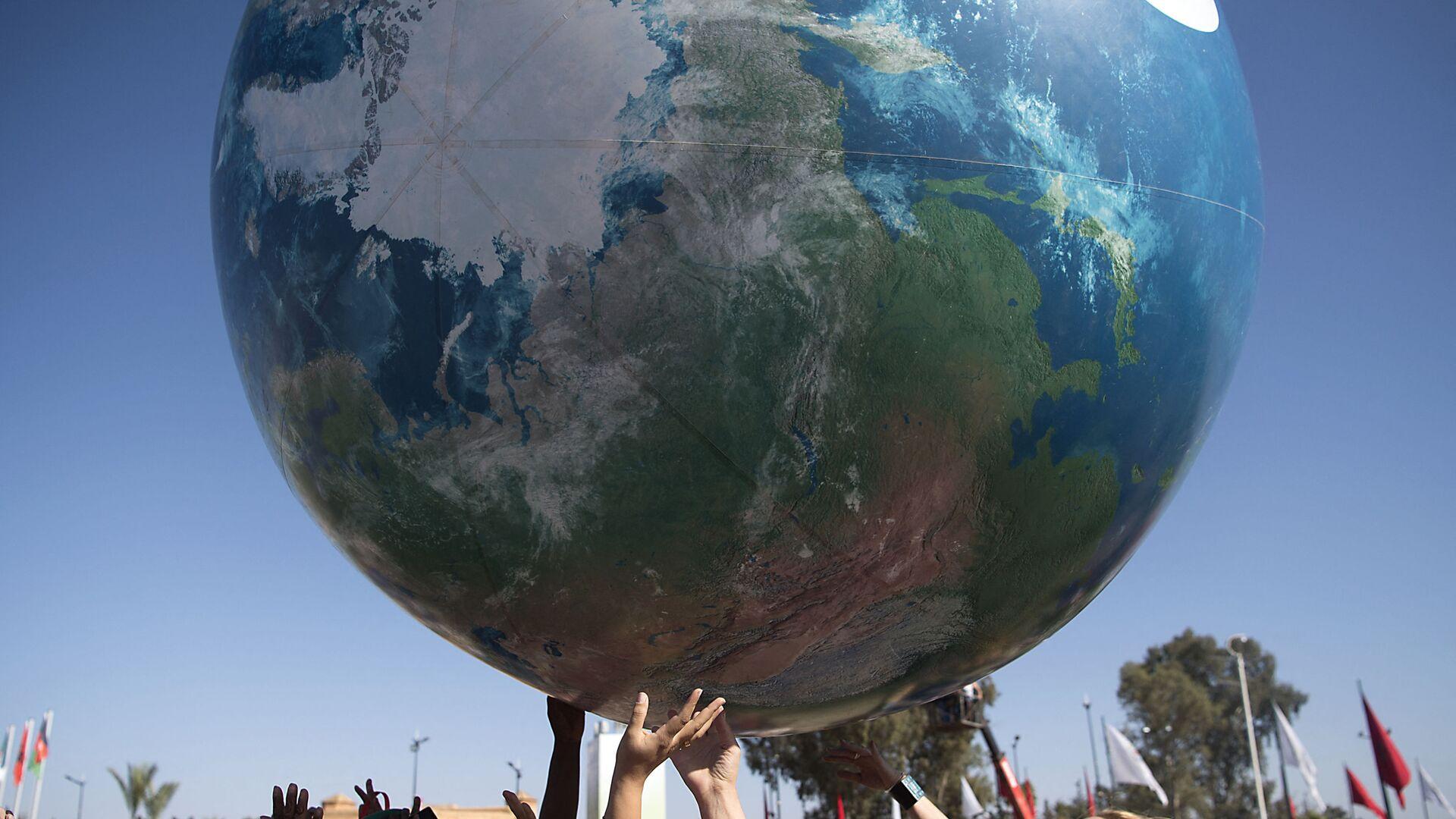 Члены всемирной конференции ООН по вопросам изменения климата с макетом Земли - Sputnik Армения, 1920, 13.10.2021