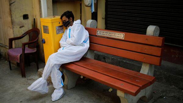 Обессиленный медицинский работник отдыхает в крематории в Нью-Дели, Индия - Sputnik Արմենիա