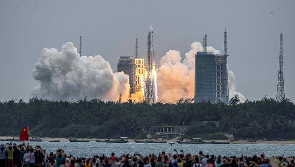 Люди наблюдают за запуском ракеты Long March 5B с основным модулем китайской космической станции Tianhe, которая стартует с космодрома Вэньчан в провинции Хайнань (29 апреля 2021). Китай - Sputnik Армения