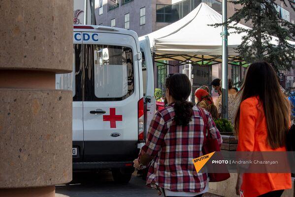 Девушки проходят мимо мобильной точки по вакцинации всех желающих на Северном Проспекте (7 мая 2021). Еревaн - Sputnik Армения