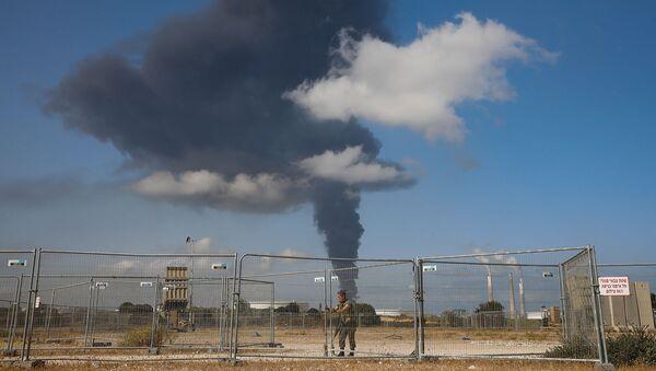Израильский солдат рядом с системой ПВО Железный купол на фоне горящего нефтяного резервуара, пораженного ракетным обстрелом из сектора Газа (12 мая 2021). Ашкелон - Sputnik Армения