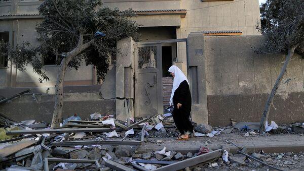 Палестинская женщина проходит мимо разрушенного от израильских авиаударов дома (12 мая 2021). Газа - Sputnik Армения