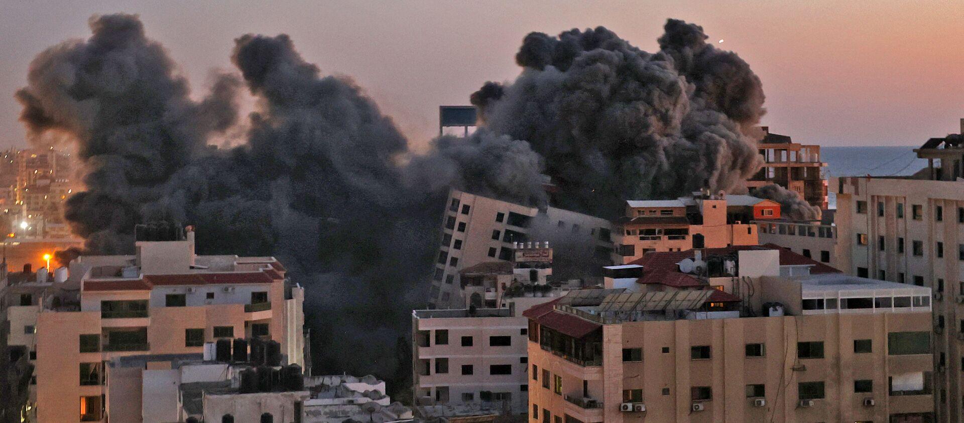 Пожарные тушат горящие многоквартирные дома после израильских авиаударов в городе Газа - Sputnik Արմենիա, 1920, 17.05.2021