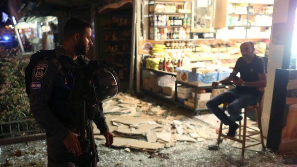 Сотрудник сил безопасности разговаривает с мужчиной на месте попадания ракеты, выпущенной из сектора Газа, в Холоне, Израиль - Sputnik Армения