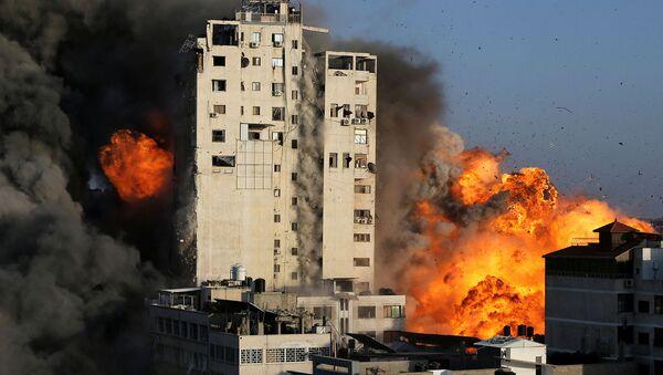 Дым и пламя поднимаются над зданием башни, разрушенным израильскими воздушными ударами на фоне вспышки израильско-палестинского конфликта в городе Газа (12 мая 2021). - Sputnik Армения
