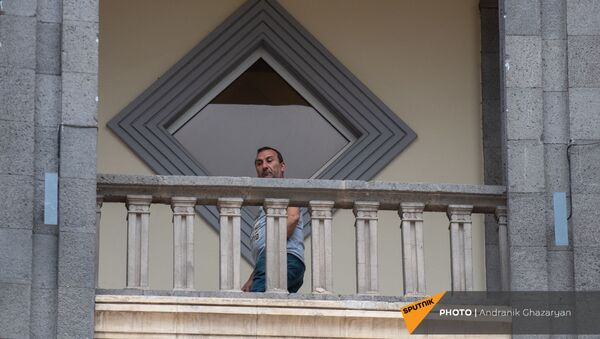 Мужчина наблюдает за митингом движения 5165 с требованием опубликовать договор с Азербайджаном (22 мая 2021). Еревaн - Sputnik Армения