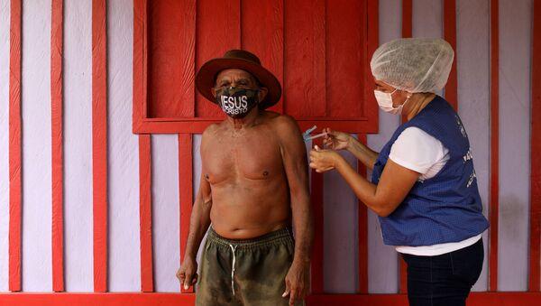 Медицинский работник Ана Кассия Оливейра де Лима применяет вакцину против коронавируса AstraZeneca (COVID-19) 75-летнему Жоао Акино Филью в день вакцинации на берегу реки Негр, Бразилия - Sputnik Армения