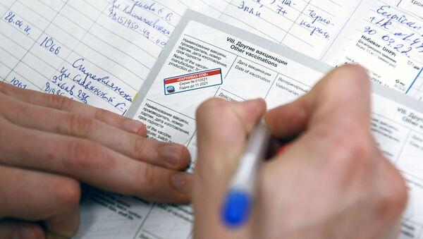 Ветеринарный врач делает отметку в паспорте животного после вакцинации от COVID-19 в ветеринарной клинике в Москве - Sputnik Արմենիա