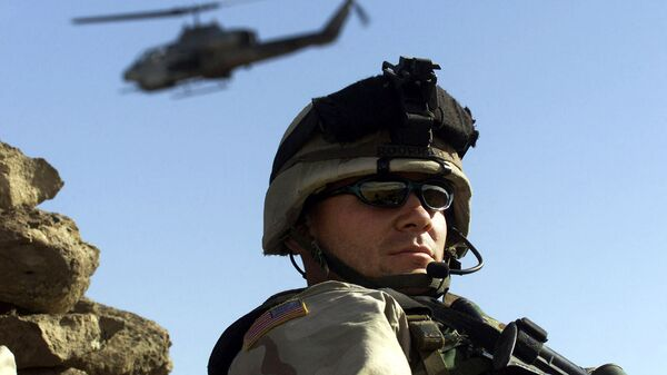 Военнослужаший армии США на фоне боевого вертолета - Sputnik Армения