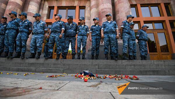 Сотрудница муниципальной службы убирает конфеты, брошенные представителями молодежного крыла АРФД во время акции неповиновения у здания правительства (10 июня 2021). Еревaн - Sputnik Արմենիա