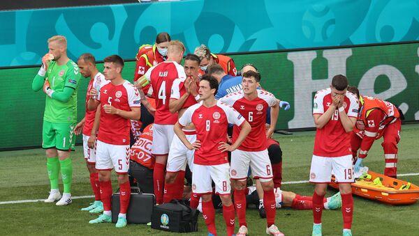 Футболисты сборной Дании стоят перед Кристианом Эриксеном, который получил серьезную травму во время 1 тура Чемпионата Европы по футболу Евро-2020 в группе Б между сборными Дании и Финляндии (12 июня 20210. Копенгаген - Sputnik Армения