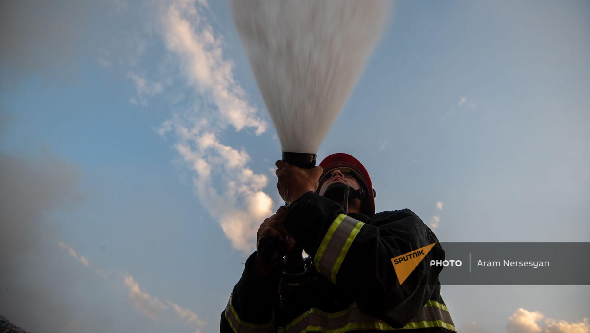 Сотрудник МЧС тушит пожар на свалке в Нубарашене - Sputnik Արմենիա, 1920, 31.08.2021