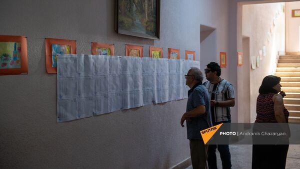 Люди изучают списки избирателей в избирательном участке 29/29 (20 июня 2021). Ариндж - Sputnik Армения