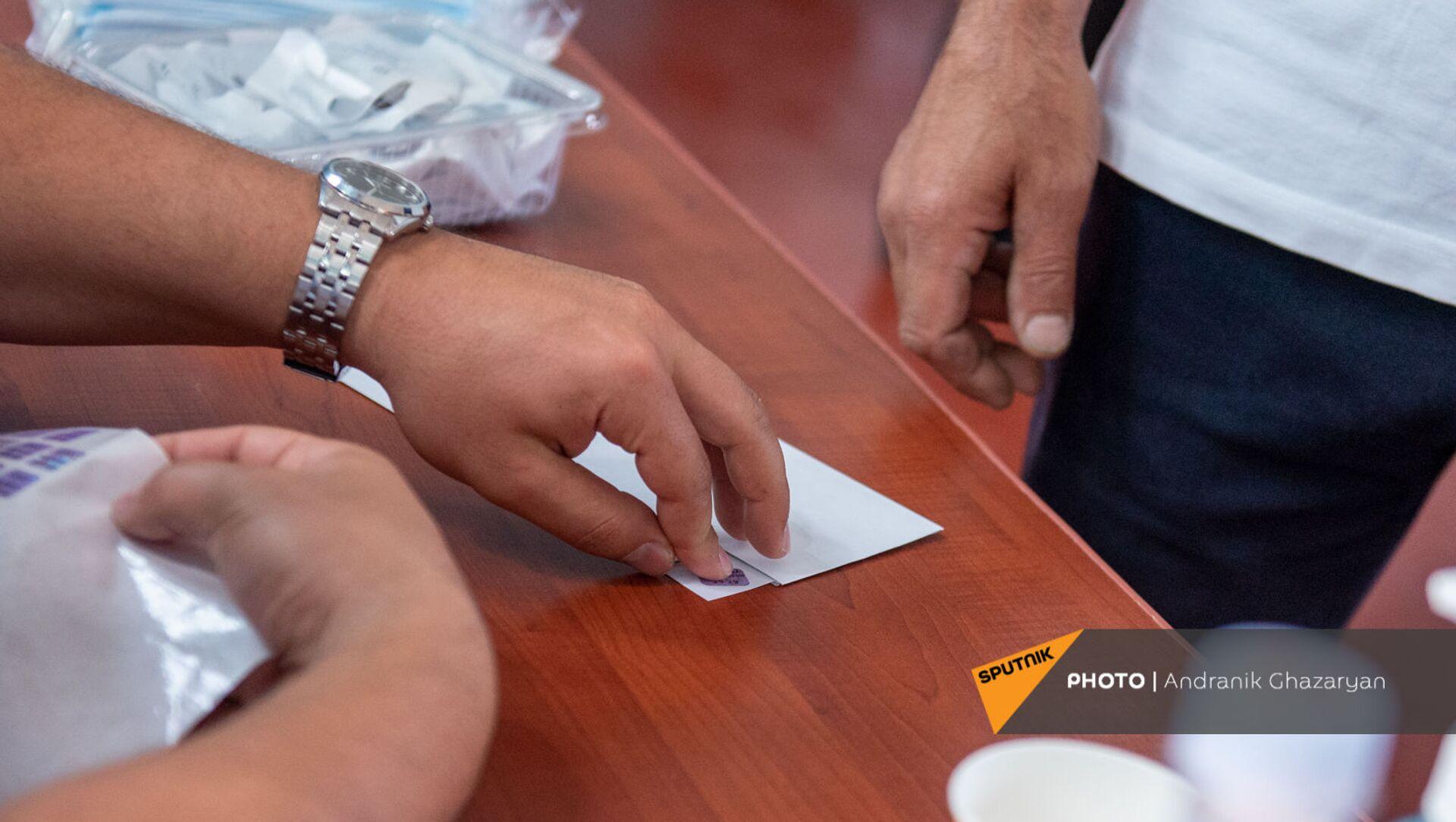 Сотрудник избирательной комиссии приклеивает наклейку на конверт с бюллетенем в избирательном участке 29/29 (20 июня 2021). Ариндж - Sputnik Արմենիա, 1920, 23.07.2021
