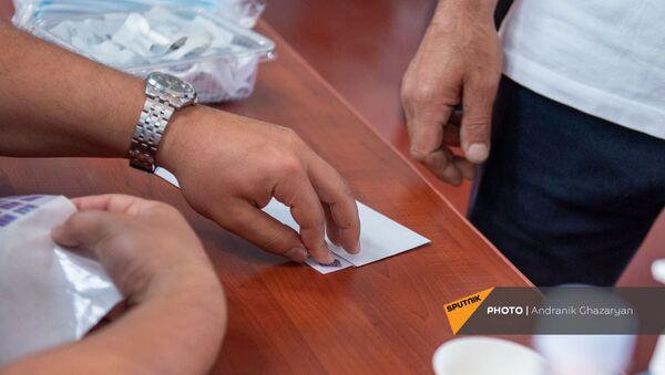 Сотрудник избирательной комиссии приклеивает наклейку на конверт с бюллетенем в избирательном участке 29/29 (20 июня 2021). Ариндж - Sputnik Արմենիա