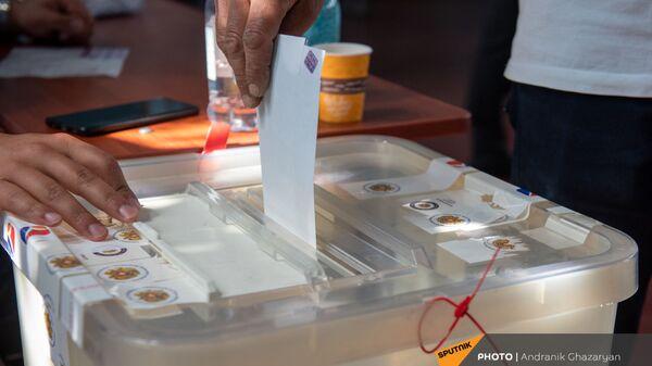 Избиратель закидывает конверт с бюллетенем в урну на участке 29/29 (20 июня 2021). Ариндж - Sputnik Армения