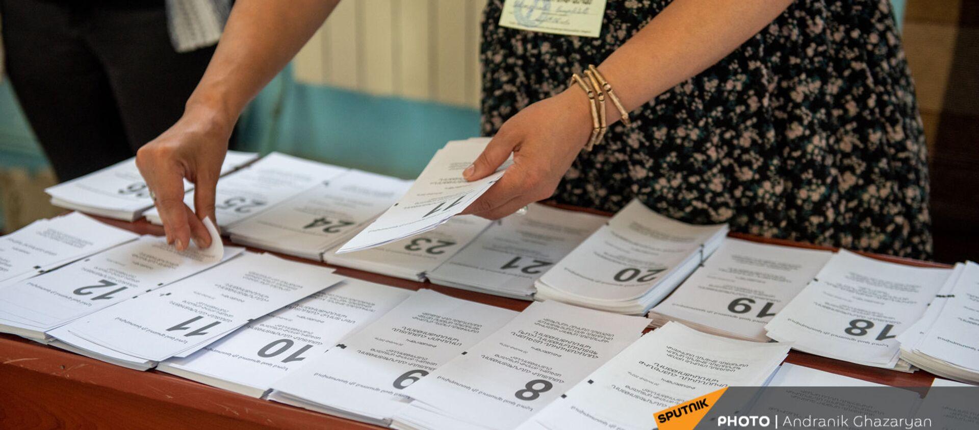 Сотрудник избирательной комиссии собирает пакет бюллетеней в избирательном участке 29/29 (20 июня 2021). Ариндж - Sputnik Արմենիա, 1920, 22.06.2021