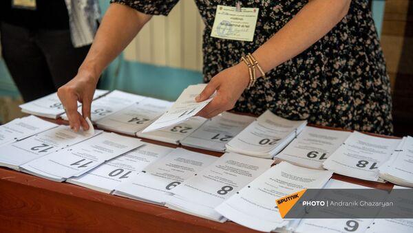 Сотрудник избирательной комиссии собирает пакет бюллетеней в избирательном участке 29/29 (20 июня 2021). Ариндж - Sputnik Армения