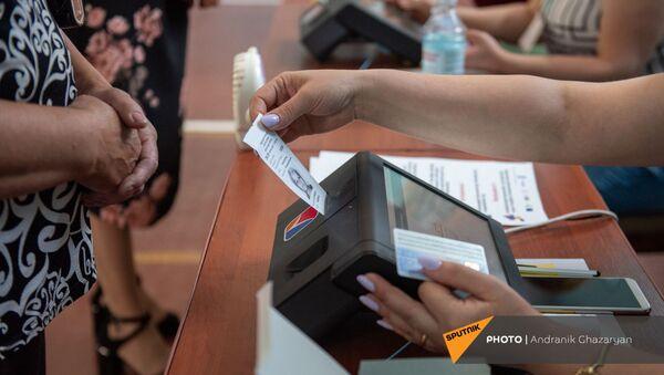 Сотрудник избирательной комиссии проверяет личность избирателя в избирательном участке 29/29 (20 июня 2021). Ариндж - Sputnik Армения