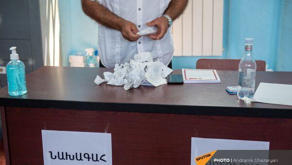 Председатель избирательной комиссии 29/29 сортирует чеки избирателей в стопку (20 июня 2021). Ариндж - Sputnik Армения