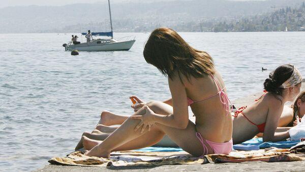 Молодая женщина наносит солнцезащитный крем на Цюрихском озере - Sputnik Армения