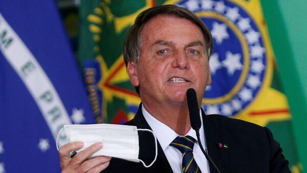 Президент Бразилии Жаир Болсонару держит защитную маску во время церемонии во дворце Планалто (10 июня 2021). Бразилиа - Sputnik Армения
