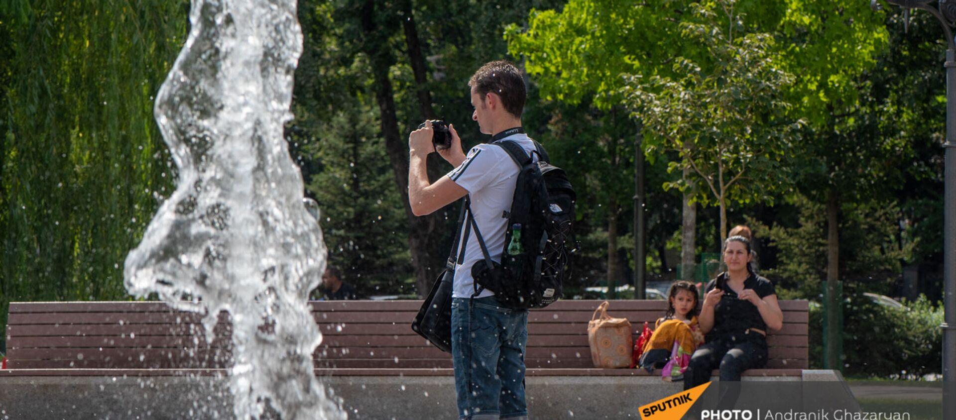 Молодой человек фотографирует фонтаны в парке 2800-летия Еревана - Sputnik Армения, 1920, 02.07.2021