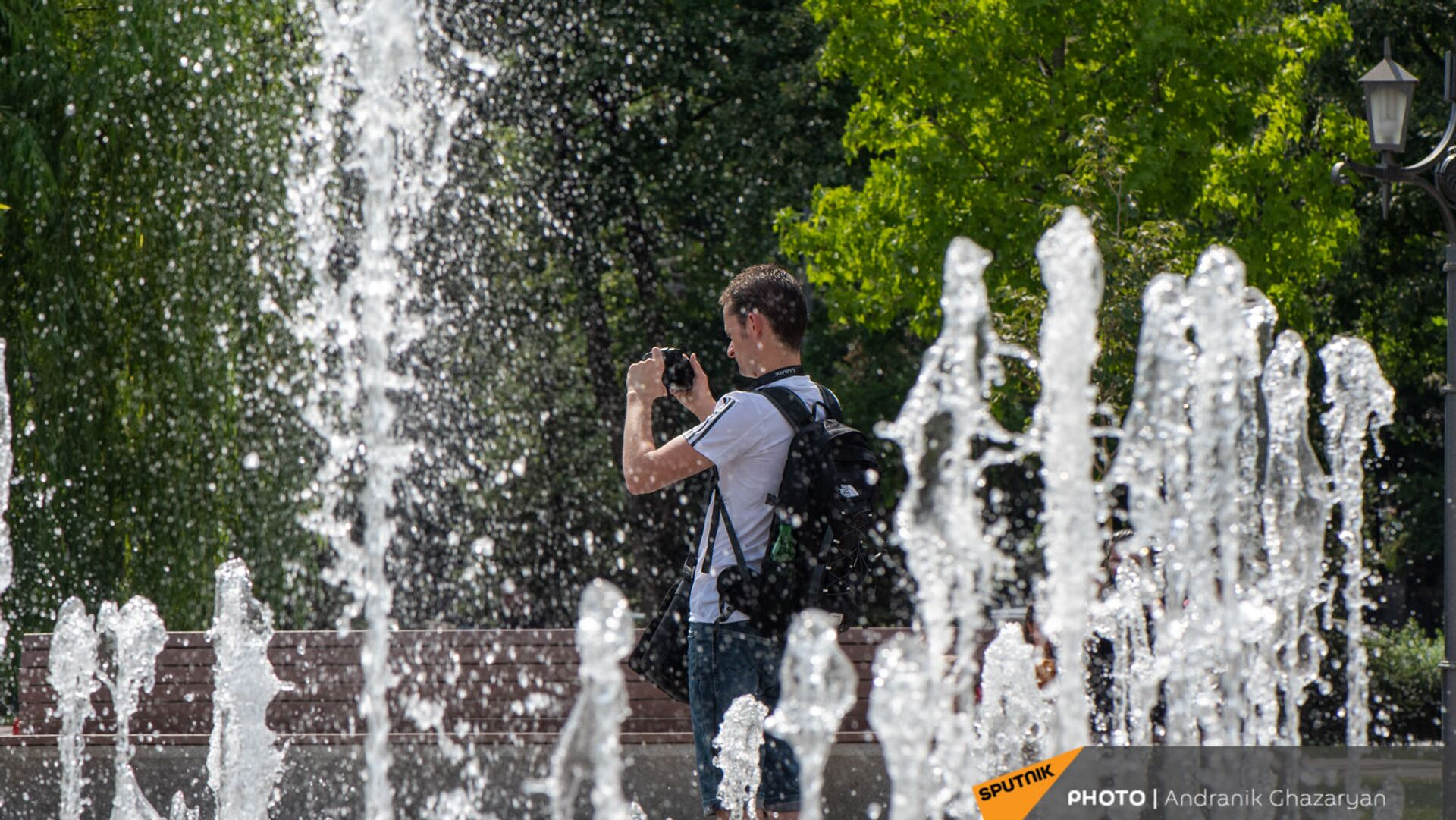 Молодой человек фотографирует фонтаны в парке 2800-летия Еревана - Sputnik Армения, 1920, 19.09.2021