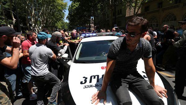 Протестующие пытаются заблокировать полицейскую машину во время митинга перед запланированным Маршем достоинства (5 июля 2021). Тбилиси - Sputnik Армения