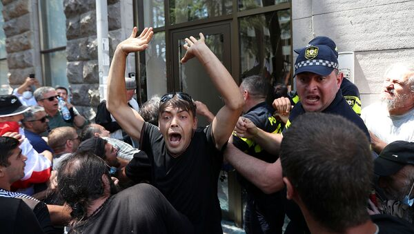 Протестующие штурмуют офис активистов ЛГБТ во время митинга перед запланированным Маршем достоинства (5 июля 2021). Тбилиси - Sputnik Армения