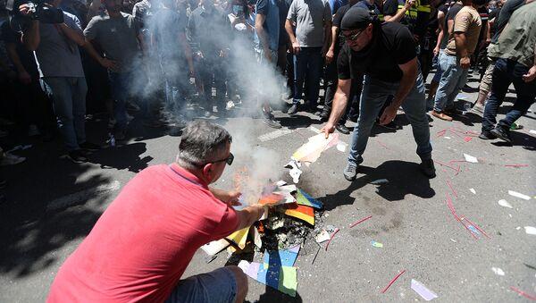Протестующие против ЛГБТ сжигают радужный баннер во время митинга перед запланированным Маршем достоинства (5 июля 2021). Тбилиси - Sputnik Армения