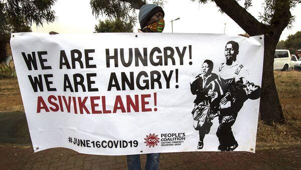 Мужчина держит плакат с надписью «Мы голодны, давайте защищать друг друга» (16 июня 2020). ЮАР - Sputnik Армения