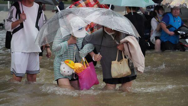 Жители провинции Ханань во время проливного дождя на дороге в Чжэнчжоу (20 июля 2021). Китай - Sputnik Армения