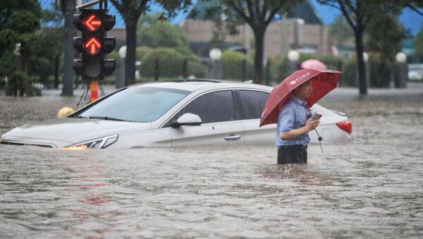 Мужчина у затопленной в результате проливных дождей машины после проливных дождей в Чжэнчжоу в центральной провинции Китая Хэнань - Sputnik Արմենիա