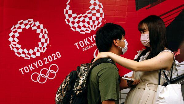 Пара на эскалаторе на фоне олимпийских баннеров на станции Китасандо в Токио - Sputnik Армения