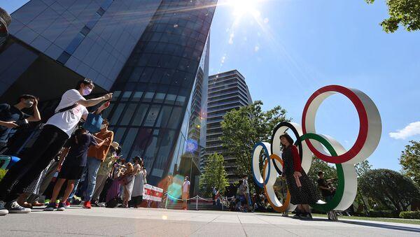 Люди форографируются на фоне Олимпийских колец в Токио - Sputnik Армения