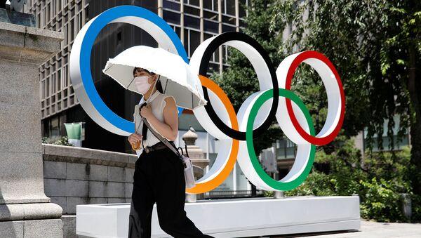 Женщина проходит мимо Олимпийских колец в Токио - Sputnik Արմենիա