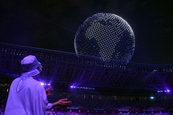 Մարզիկներն ու կամավորները նայում են օլիմպիական մարզադաշտի երկնքում դրոնների կազմած գլոբուսին - Sputnik Արմենիա